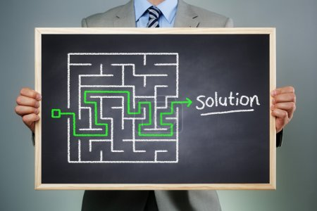 Photo for Business strategy businessman holding a blackboard planning and finding a solution through a chalk drawing of a maze - Royalty Free Image