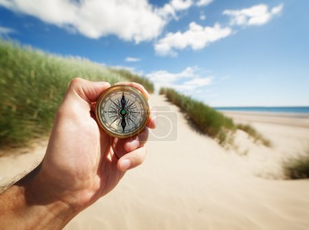 Photo for Hand holding a compass on the beach by sea concept for guidance, direction, and adventure - Royalty Free Image