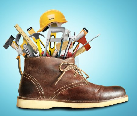 Photo for Tools and construction helmet in a big Shoe - Royalty Free Image