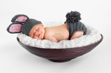 Photo for Eight day old smiling newborn baby boy wearing bunny ears and a bunny tail sleeping on his stomach in a basket - Royalty Free Image