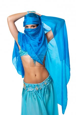 Exotic belly dancer peeking from behind a blue veil wrapped
