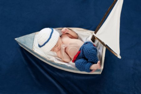 One week old newborn baby boy wearing a white and blue sailor hat.