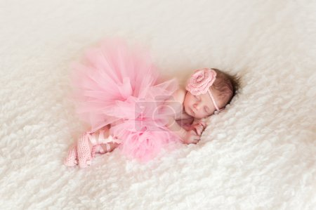 Sleeping newborn baby girl wearing a pink crocheted headband and tutu.