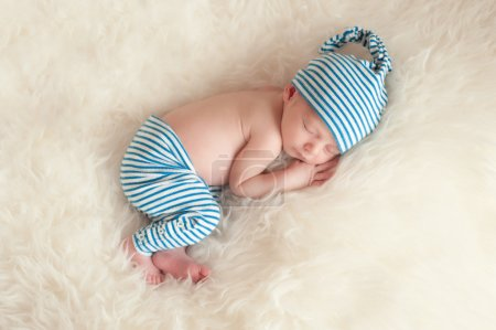 Newborn baby wearing blue and white striped pajamas and sleeping on off white faux fur.