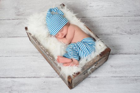 Newborn baby wearing blue and white striped pajamas and sleeping in a vintage, wooden, soda pop crate.