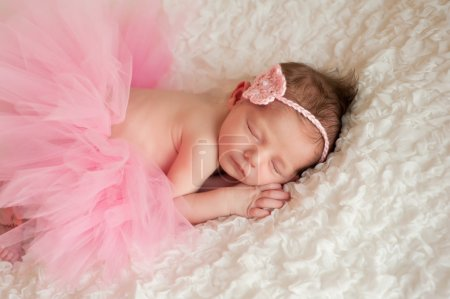 Newborn baby girl wearing a pink crocheted headband and tutu.
