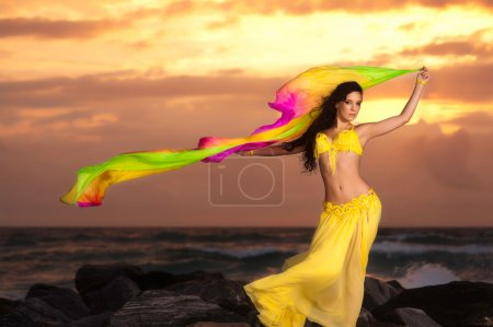 A beautiful bellydancer poses with a flowing yellow silk veil and standing on a rocky bank in front of the Atlantic Ocean