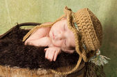 Newborn Baby Boy Wearing a Fishing Hat and Sleeping in a Wooden Bucket