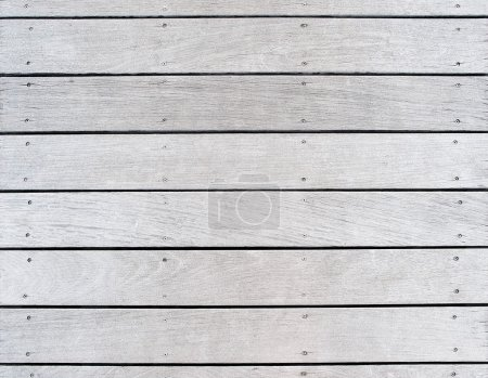 A boat dock's old weathered and faded wood decking.