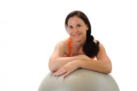 Brunette woman leaning on a gray Pilates exercise ball.