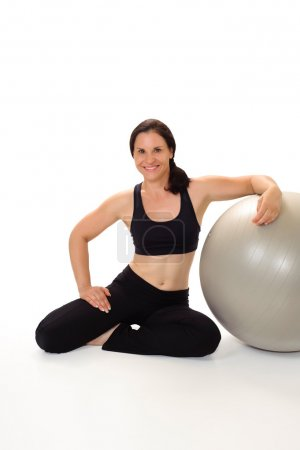 Woman wearing workout clothing, smiling and leaning on a Pilates exercise ball.