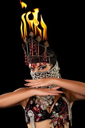 Head and Shoulders shot of an exotic belly dancer wearing a red and black costume with hijab and fire headdress
