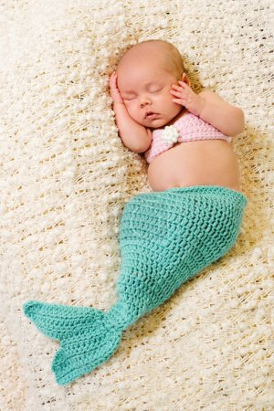 Newborn baby girl wearing a crocheted turquoise and pink mermaid costume, sleeping on a cream colored blanket.
