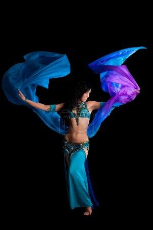 Photo pour Une danseuse exotique portant un costume bleu sarcelle et bleu royal. Elle danse avec un voile de soie bleu et violet. Tourné en studio sur fond noir . - image libre de droit