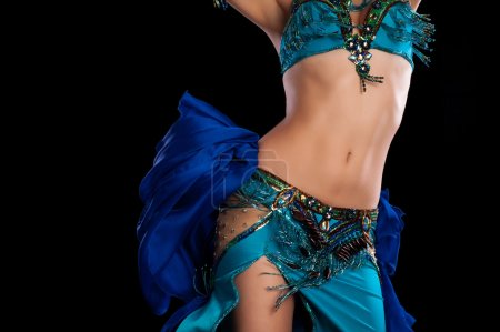 Photo for Torso of a female belly dancer wearing a teal blue costume and shaking her hips. Isolated on a black background. - Royalty Free Image