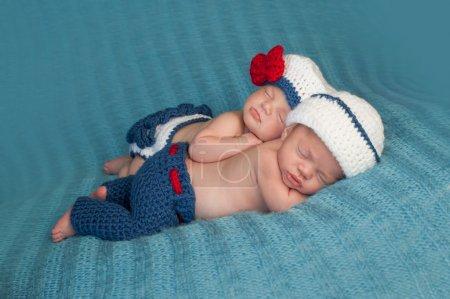 Photo pour Cinq semaines de sommeil garçon et fille jumeaux fraternels nouveau-nés. Ils portent des tenues de marin au crochet. Un bébé est couché sur le ventre et l'autre est appuyé sur le dessus de sa sœur . - image libre de droit