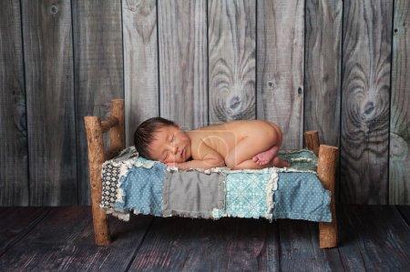 Photo pour Portrait d'un garçon nouveau-né âgés de neuf jours. il dort sur un lit miniature avec un patchwork. tourné en studio sur fond de bois rustique. - image libre de droit