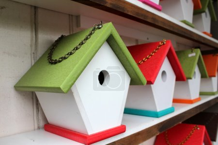 Handcrafted rustic birdhouses with bright colorful roofs and link chains for hanging them up around the yard to attract our feathered friends to nest in.