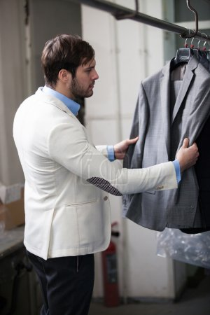 Handsome man shopping for clothes at a store.