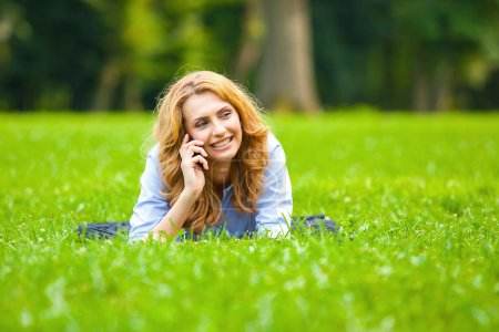Blonde woman speaking at cellphone in green grass