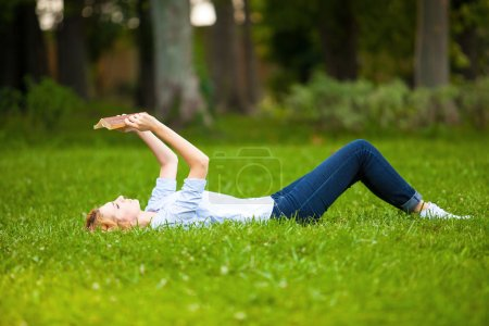 woman lying in grass and reading a book