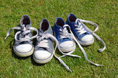 Two pairs of old sneakers on grass background