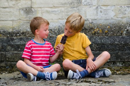 Two boys sharing an ice lolly