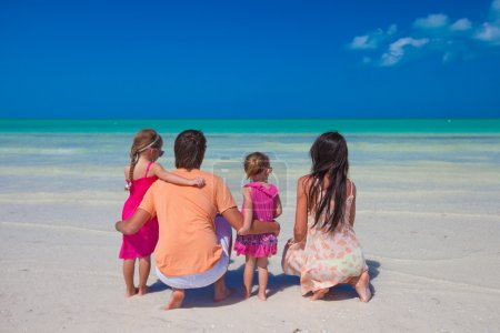 Rear view of young family with two kids on caribbean beach vacation