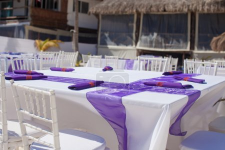 White wedding table decorated with purple bows on sandy beach