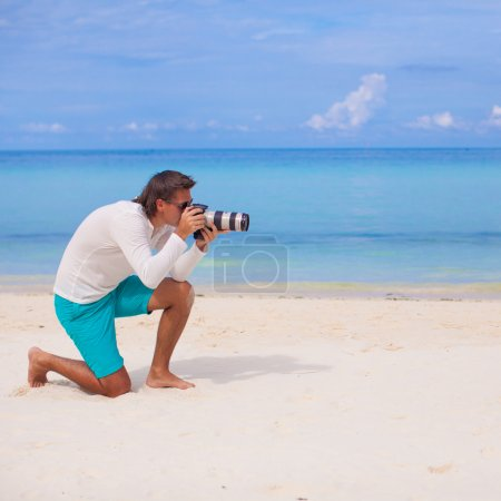 Profile of young man with camera in hand on beautiful white sandy beach