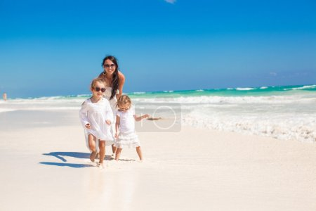 Young mother and her little daughters walking on tropical white beach