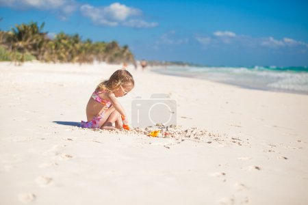 Adorable little girl in swimsuit playing at tropical carribean beach