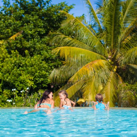 Two daughters and young mother relaxing in the luxury quiet swimming poo