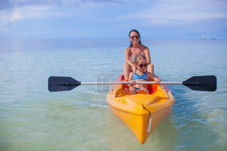 Two kids with their mom at a boat floating in the clear sea