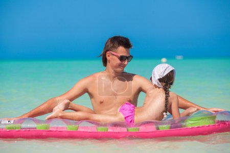Little girl with young father on an air mattress in the sea
