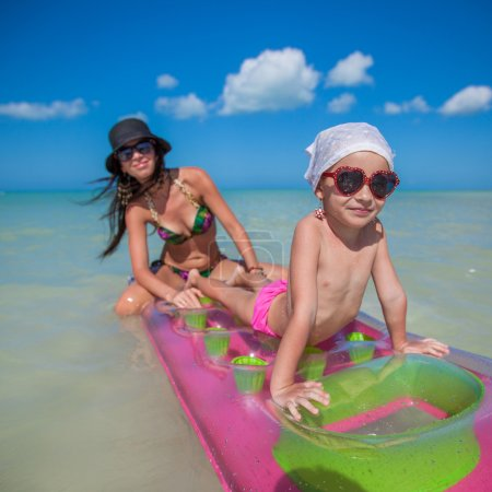 Little girl with young mother on an air mattress in the sea