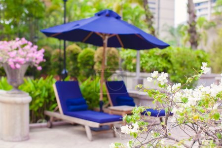 Two blue loungers with umbrellas near swimming pool in luxury hotel