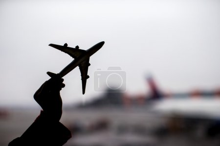 Photo for Close up hand holding an airplane model background the airport - Royalty Free Image
