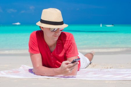 Young man with phone on tropical white beach