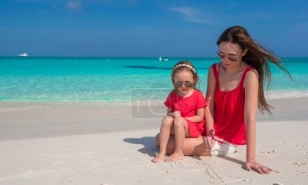 Mother and daughter relaxing at tropical beach