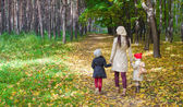Little cute girls and young mother in autumn park