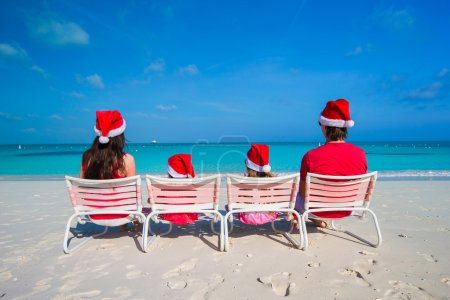 Happy family of four in Santa Hat on summer vacation