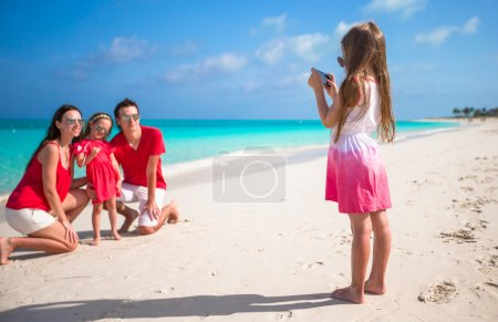 Photo for Little girl photographing her dad and sister on the beach - Royalty Free Image