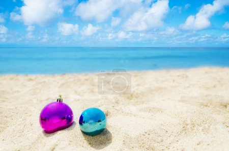 Two Christmas balls on the beach - holiday concept