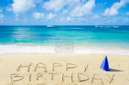 """Photo for Sign """"Happy Birthday"""" with hat on the sandy beach by the ocean - Royalty Free Image"""