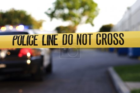 Photo for Crime scene tape in the foreground with a blurred police car in the background at a crime scene. - Royalty Free Image