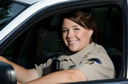 Photo for A friendly looking female police officer sits and smiles in her patrol car. - Royalty Free Image