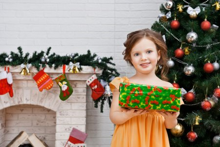 Little girl with a gift near the Christmas tree