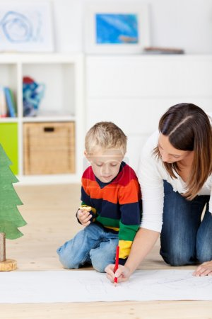 Boy Looking At Mother Drawing On Chart Paper