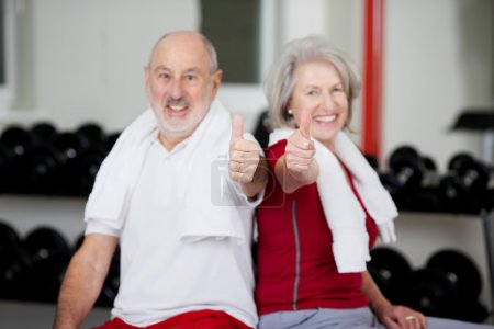 Senior Couple Showing Thumbs Up Sign In Gym